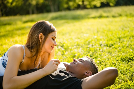 couple dating: Woman holding stem and playing with it on mans face - couple on date in nature Stock Photo