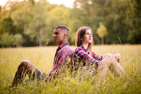 grassfield: Young multi racial couple sitting in grass and leaning with their backs - outdoor in evening nature