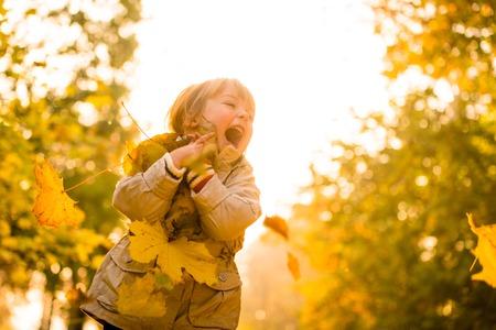 persona feliz: La niña disfruta de la captura de las hojas que caen en otoño al atardecer Foto de archivo