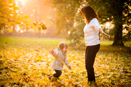 family outside: Mom and child having great time playing together in autumn - girl is running around mother Stock Photo