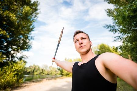 lanzamiento de jabalina: Determinación - visión de gran angular de un joven lanzando una jabalina al aire libre