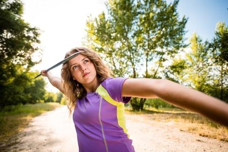 lanzamiento de jabalina: Amplio ángulo de visión de una mujer joven lanzando una jabalina - al aire libre en un día soleado