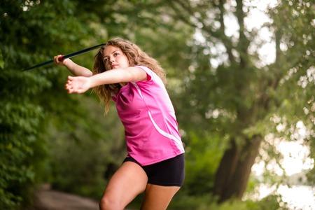 lanzamiento de jabalina: Joven deportiva que lanza la jabalina practicar su técnica en un bosque rural, cerca vista de tres cuartos