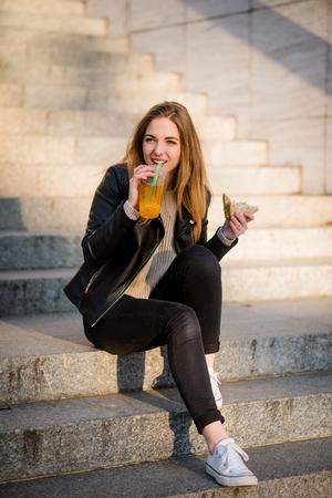 niña comiendo: La muchacha adolescente comiendo sándwich y beber jugo al aire libre que se sienta en las escaleras Foto de archivo