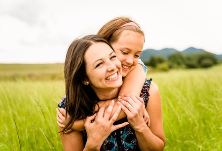 Mother and child are hugging and having fun outdoor in nature photo