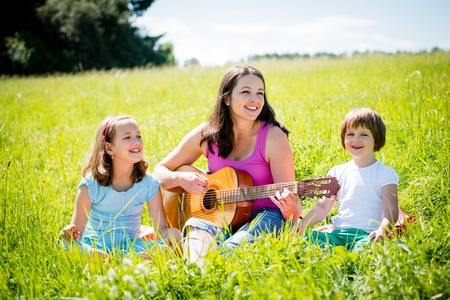 Woman playing guitar to her children in nature on sunny summer day Reklamní fotografie