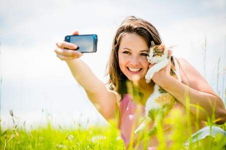 Woman taking photo with mobile phone camera of herself and her cat - outdoor in nature photo