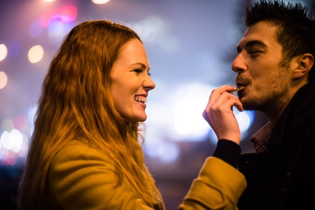 couple outdoor: Couple on date - woman feeds her boyfriend with chocolate in street at winter night Stock Photo