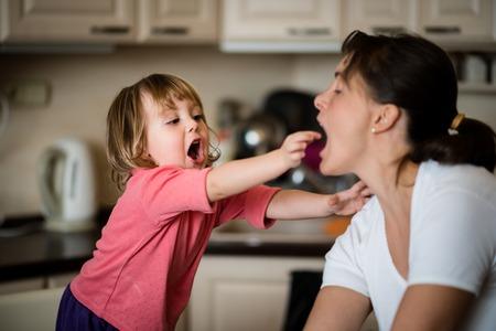 trozo de pastel: Niño que da a su madre al gusto pedazo de pastel en la cocina