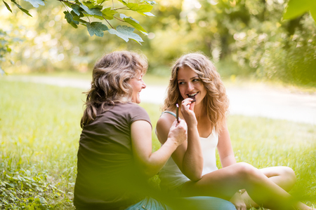 Biting chocolate. Mother and daughter enjoying leisure time. Stock Photo