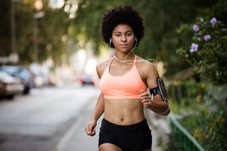 Fitness girl running on sidewalk, enjoying music. Reklamní fotografie