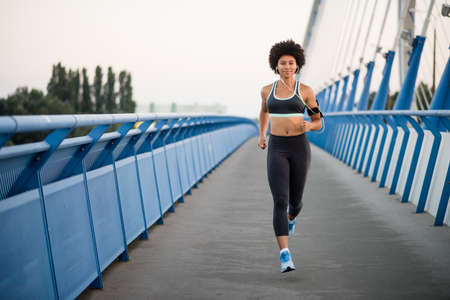 earphone: Young woman running outdoors on a modern bridge