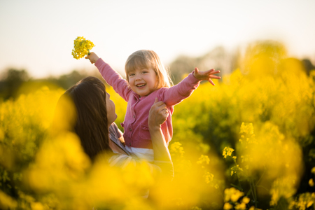Carefree baby and mother on nature in rapeseed field Stock Photo