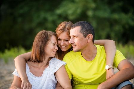 彼女の両親を抱いて笑顔の大人の娘。家族の結合。