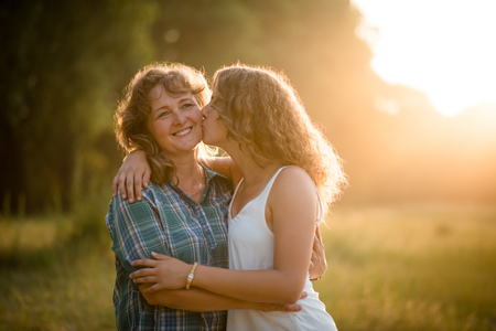 Teenage daughter kissing her mature mother