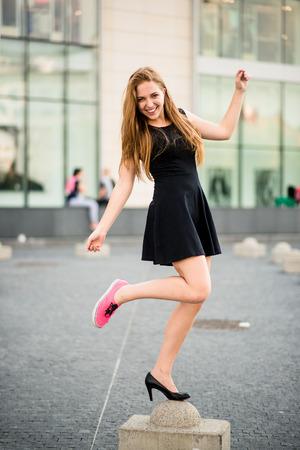 girl legs: Shoe dilemma - sneakers versus high heels Stock Photo