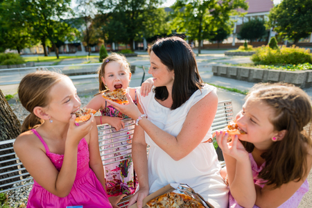 Family eating pizza together. Sharing concept. photo