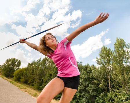 lanzamiento de jabalina: Mujer joven que lanza una jabalina en la naturaleza