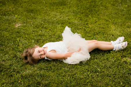 Cute little girl is lying on green meadow 版權商用圖片