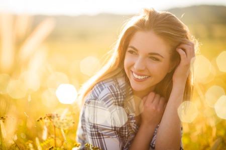 Authentiek zonnig portret van jonge mooie vrouw buiten in de natuur Stockfoto
