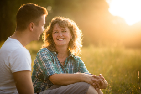 senior adult woman: Beautiful senior woman and her adult smiling son sitting in park
