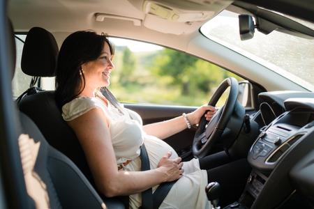 Zwangere vrouw die haar auto rijdt, draagt veiligheidsgordel.