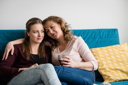 Mother and teenage daughter hugging on sofa at home Banque d'images
