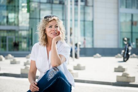 Thoughful mature woman sitting outdoors Stock Photo