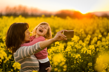 Mother holding girl child in arms, clicking selfie. Stock Photo