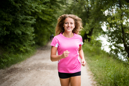 Young fitness woman running through the forest