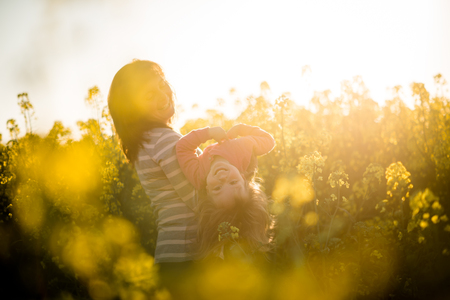 Mother and baby having fun in the rapeseed field photo