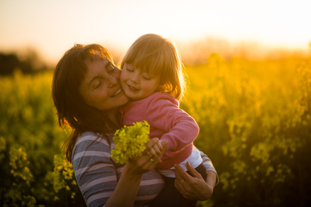 Mother with cute smiling daughter in the rapeseed field during sunset photo