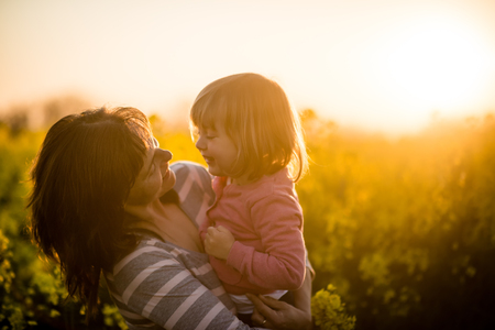 Portrait of a smiling mother with baby girl at sunset background photo