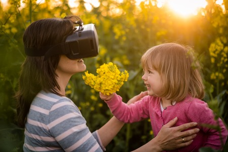 Woman looking through VR device and playing with her daughter photo