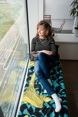 undisturbed: Senior smiling woman sitting alone near the window