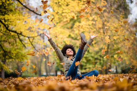 Herfst vrouw met opgeheven armen zitten