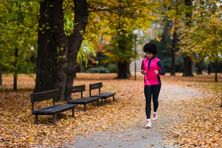 Sporty woman using phone while running