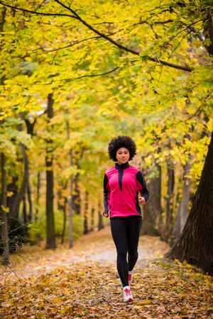 Teenager jogging in an autumn park Stock Photo