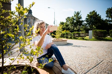 Mature woman sitting outdoors, clicking a selfie.