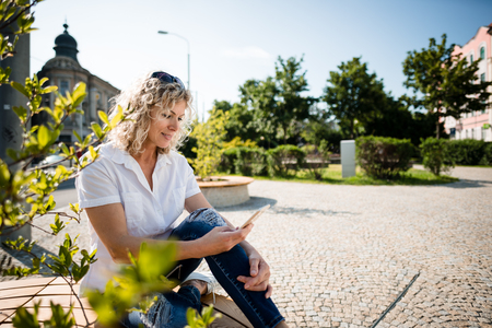 Woman sitting alone in city park using phone