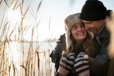 Affectionate couple embracing near frozen lake