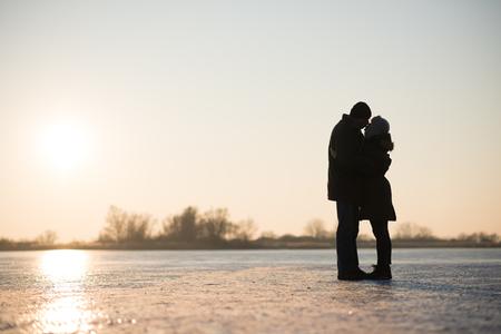 Pareja besándose y abrazándose en el lago congelado Foto de archivo - 85699436