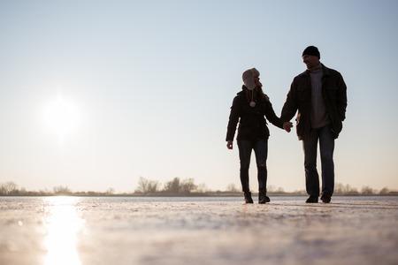Pareja que habla un paseo sobre el lago congelado Foto de archivo - 85545554