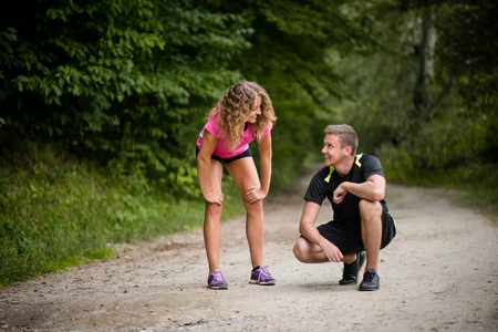 Joggers resting on gravel trail after overtraining