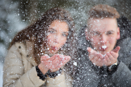 Young couple in love blowing snow away