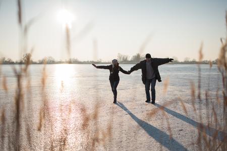 Couple stepping carefully on frozen lake Stock Photo