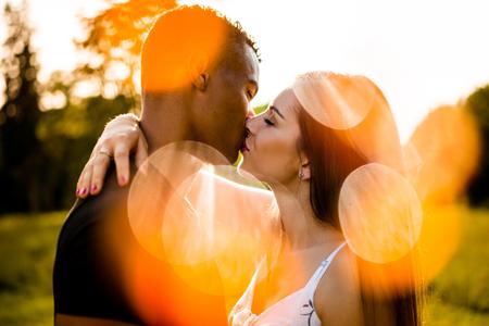 Pareja de raza mixta besándose al aire libre