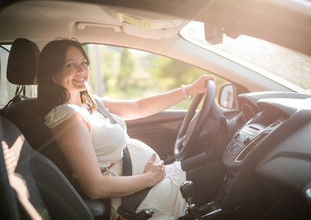 Beautiful smiling pregnant woman sitting in car Stok Fotoğraf - 93955897