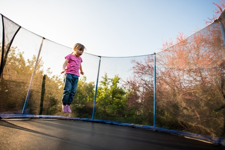 Girl afraid of jumping on trampoline bed Stock Photo