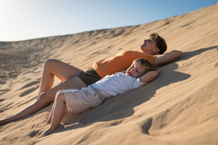 Mother and son relaxing on sand dune under blue sky